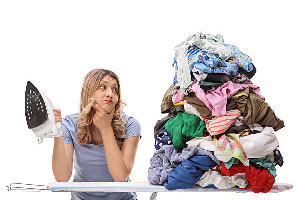 woman looking at a pile of clothes - ironing stock photos and pictures