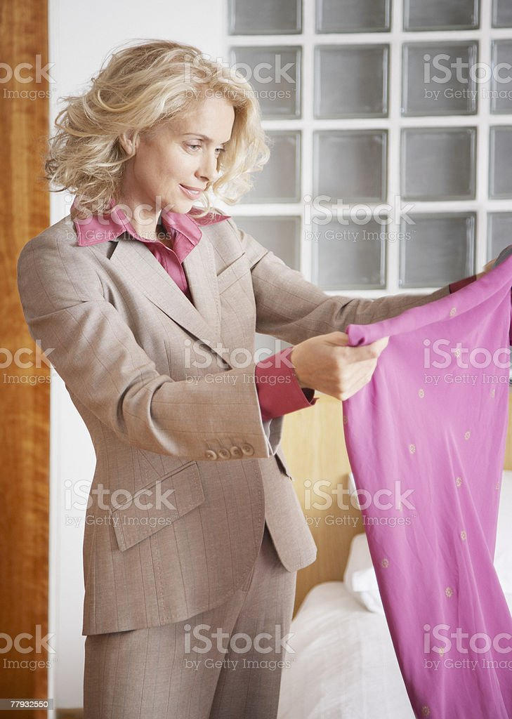 Woman looking at a skirt in bedroom 免版稅 stock photo