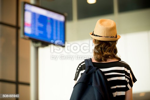 469824732istockphoto Woman looking at airport flight information board 508465940