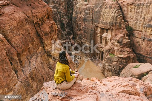 Young Caucasian woman  looking at Al-Khazneh in Petra from above