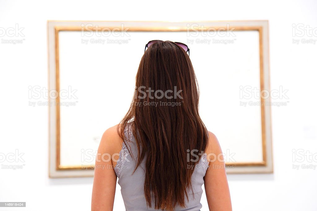 Woman looking at art painting in museum stock photo