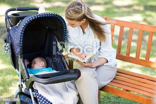 Woman holding book while looking at baby sleeping in carriage outdoors