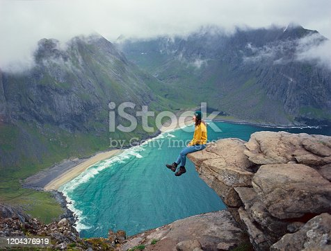 Young Caucasian woman looking at beach on Lofoten island, Norway