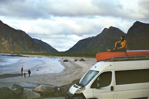 Woman looking at  beach on Lofoten islands from camper van stock photo