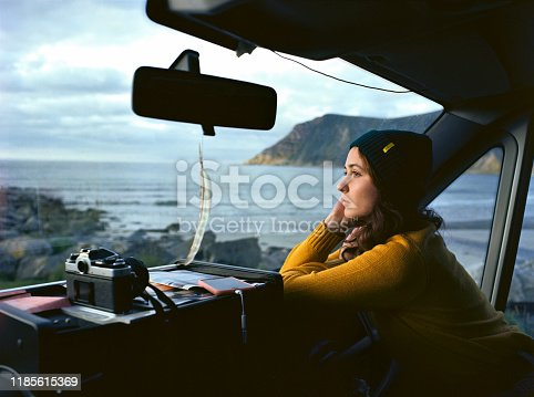 Young Caucasian woman  looking at  beach on Lofoten islands from camper van