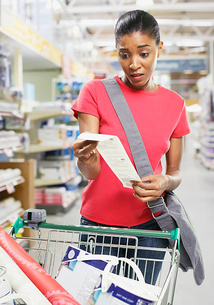 Woman looking at bill in store stock photo