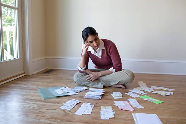 kobieta, patrząc na rachunki i rachunki na podłodze - duża grupa obiektów zdjęcia i obrazy z banku zdjęć