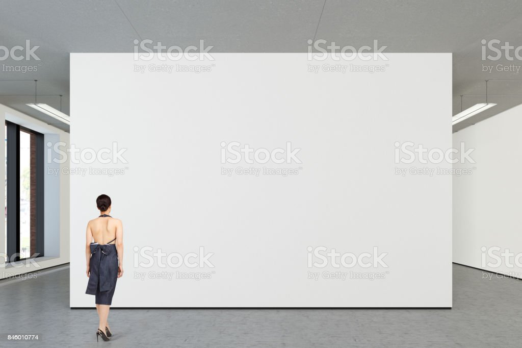 Woman looking at blank poster in modern gallery stock photo