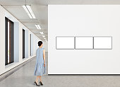 Woman looking at three blank horizontal posters in modern gallery. Posters isolated with clipping path. 3d illustration