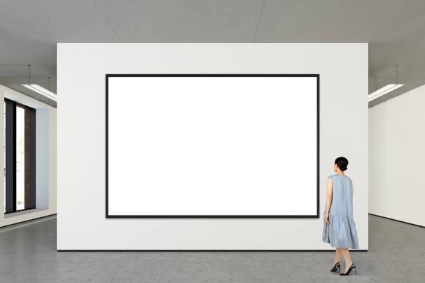 vrouw kijken naar lege poster in moderne galerie - raam bezoek stockfoto's en -beelden