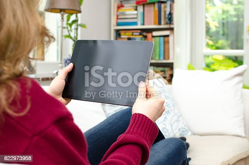 istock Woman looking at blank tablet computer screen with copy space 622973958