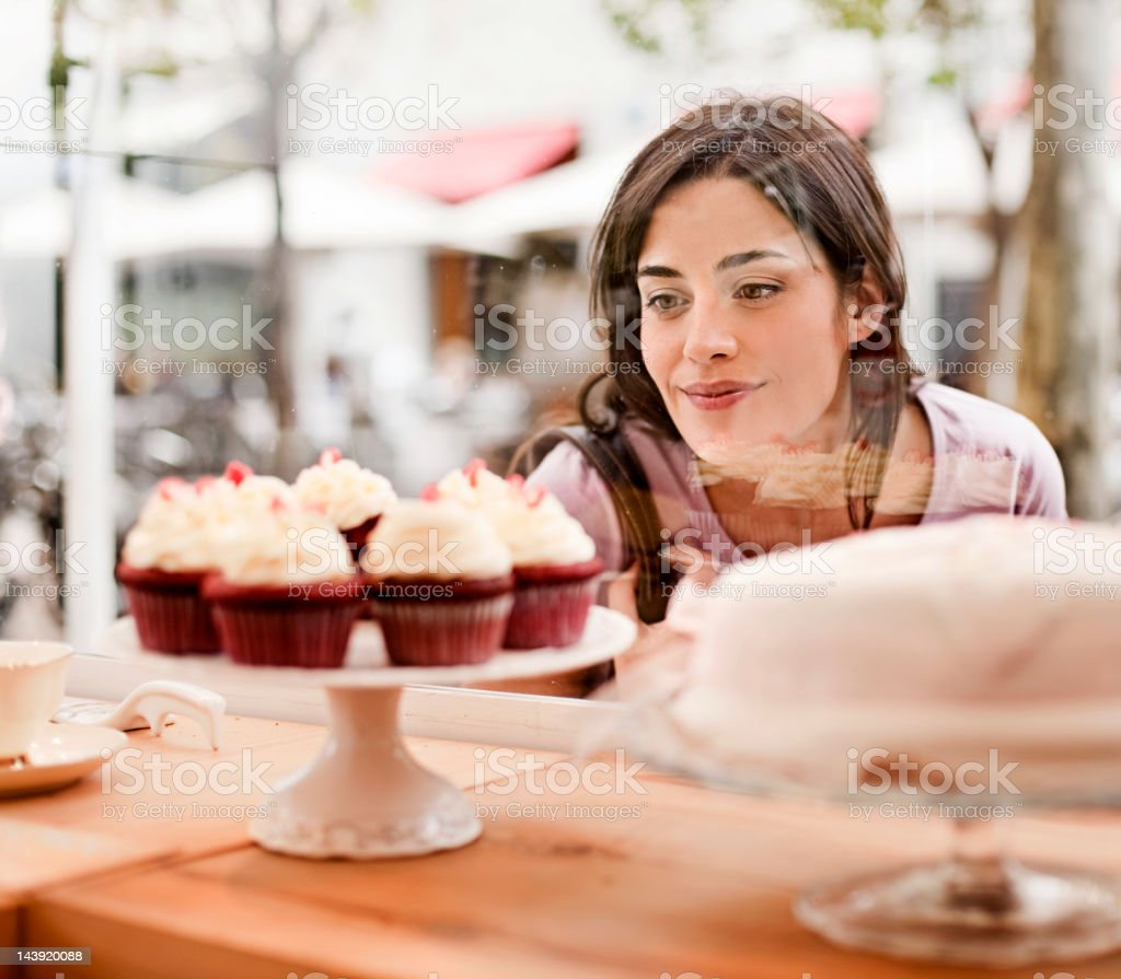 Woman looking at cake display in window stock photo