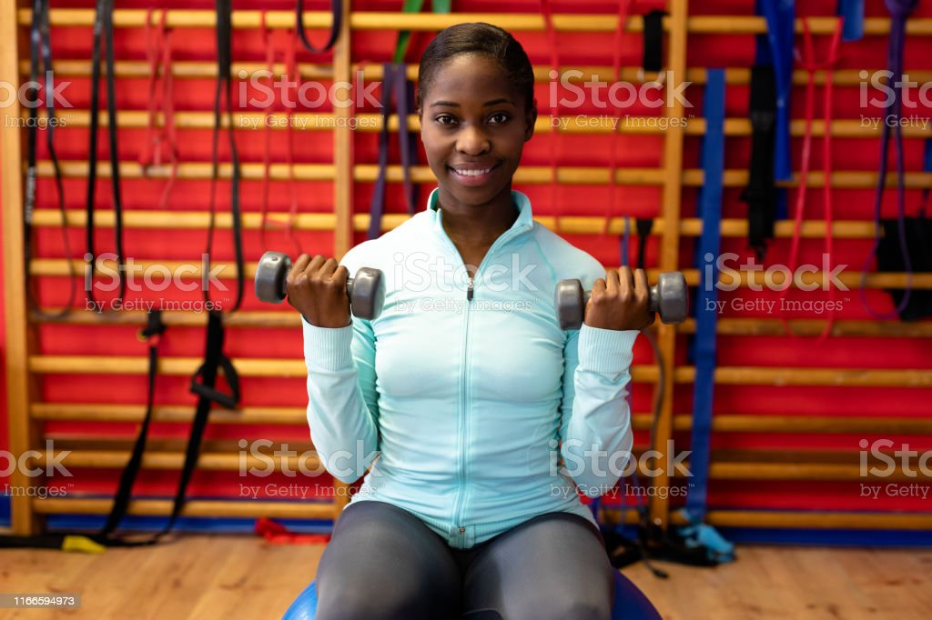 Happy woman looking at camera while exercising with dumbbell in...
