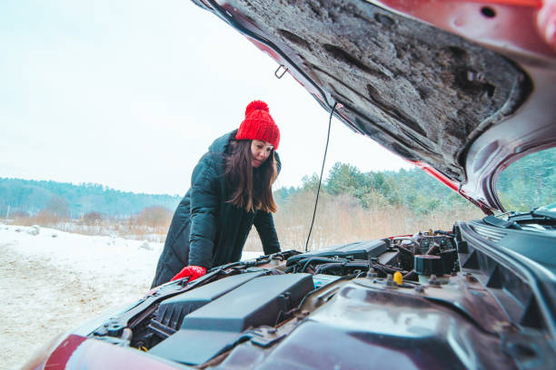 woman looking at car engine road assistance concept winter season stock photo