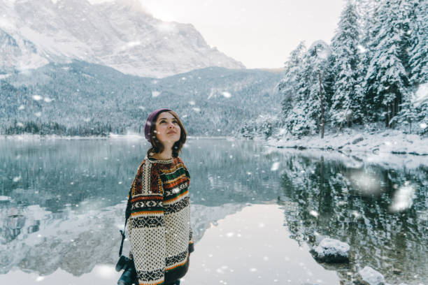 Woman looking at Cauma lake in Switzerland in winter stock photo