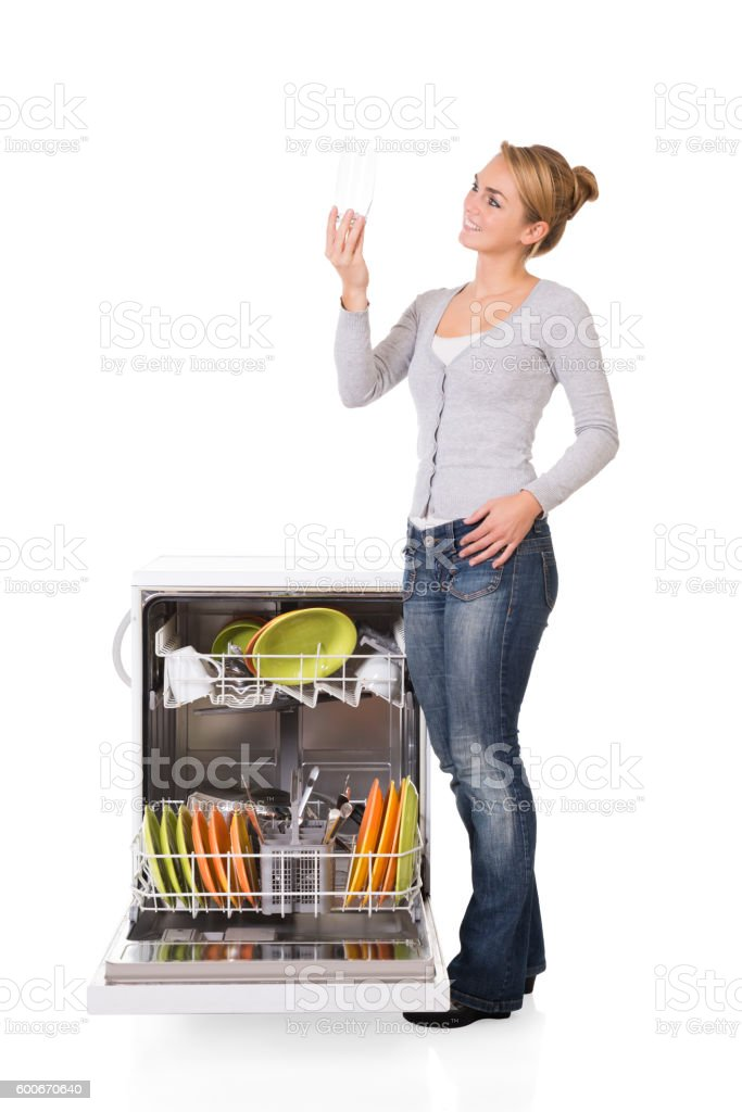Woman Looking At Clean Glass While Standing By Dishwasher stock photo