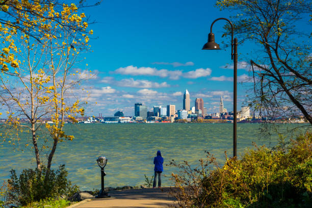 woman looking at cleveland skyline from park - eriesee stock-fotos und bilder