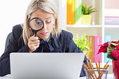 istock Woman looking at computer through a magnifying glass 518297147