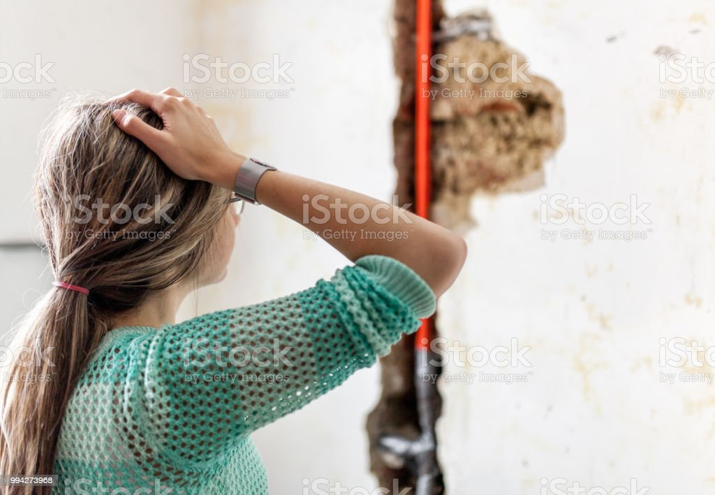Woman looking at damage after a water pipe leak stock photo