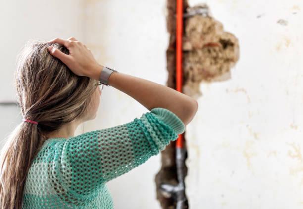 Frau, die bei der Beschädigung nach ein Wasserrohr Leck – Foto