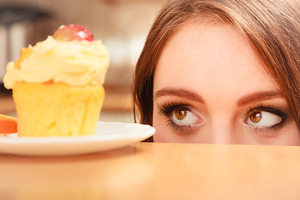 Woman looking at delicious sweet cake. Gluttony. stock photo