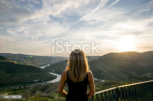 Woman looking at Douro river and valley at sunset during the harvest season. Casal de Loivos viewpoint.