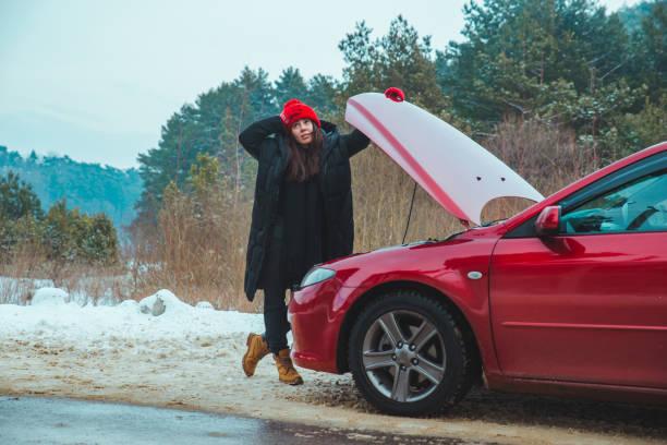woman looking at engine broken car at winter road side stock photo
