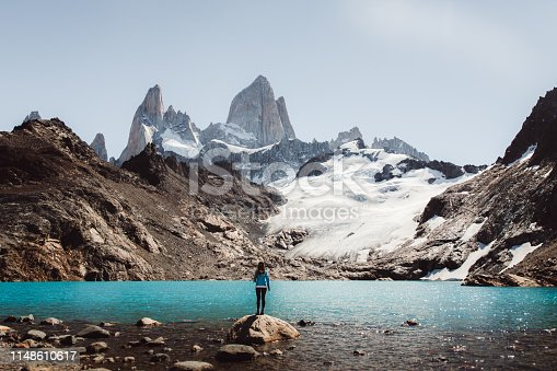 Young woman enjoying a day at Argentinian Patagonia - hiking to Fitz Roy mountain and lagoon De Los Tres during bright warm summer day