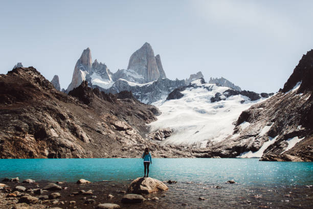 Woman looking at Fitz Roy mountain and turquoise lagoon in El Chalten, Argentina stock photo