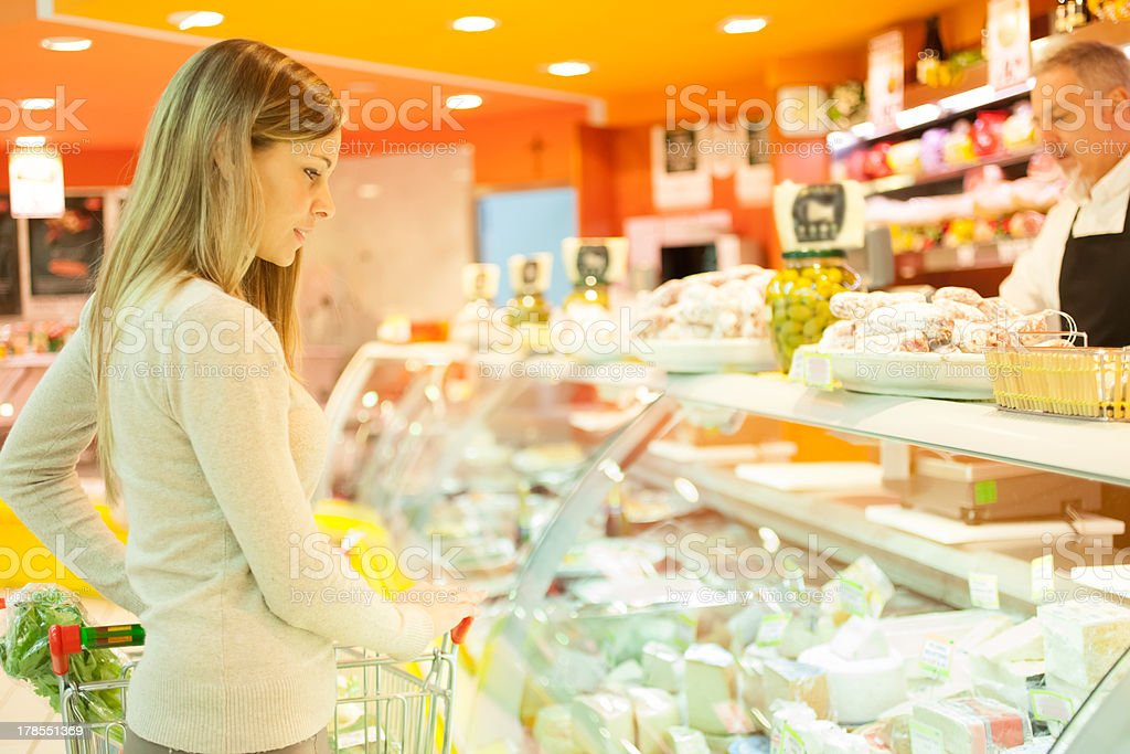 Woman looking at fresh deli in the supermarket stock photo