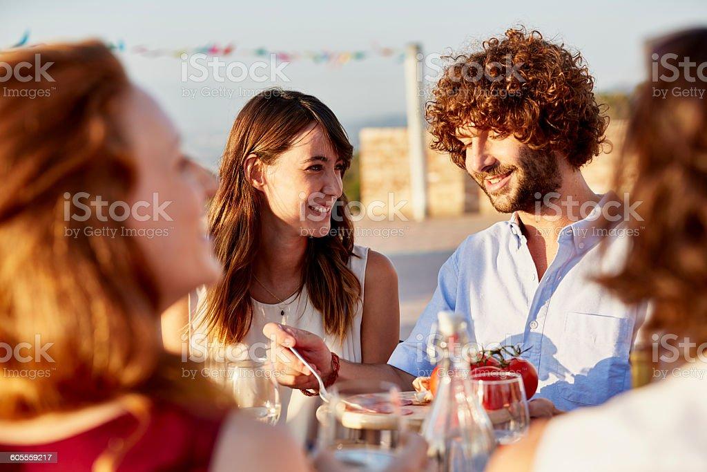 Smiling young woman looking at friend having food at social gathering