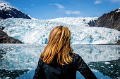 Lonely woman looking at Holgate glacier in the Kenai Fjords National Park, Alaska