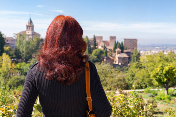 Woman Looking at Granada Granada, Spain - October 25, 2018: A redheaded woman enjoying the view of Alhambra, Granada. palace of charles v stock pictures, royalty-free photos & images