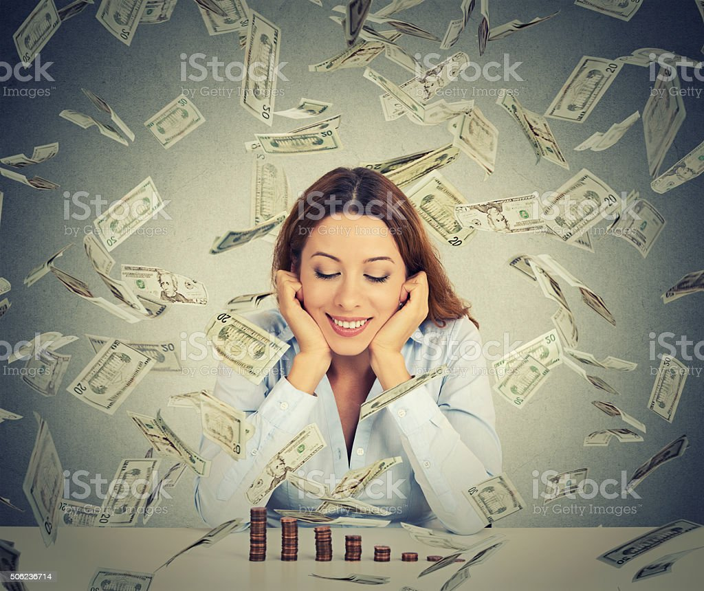 woman looking at growing stack of coins under money rain stock photo