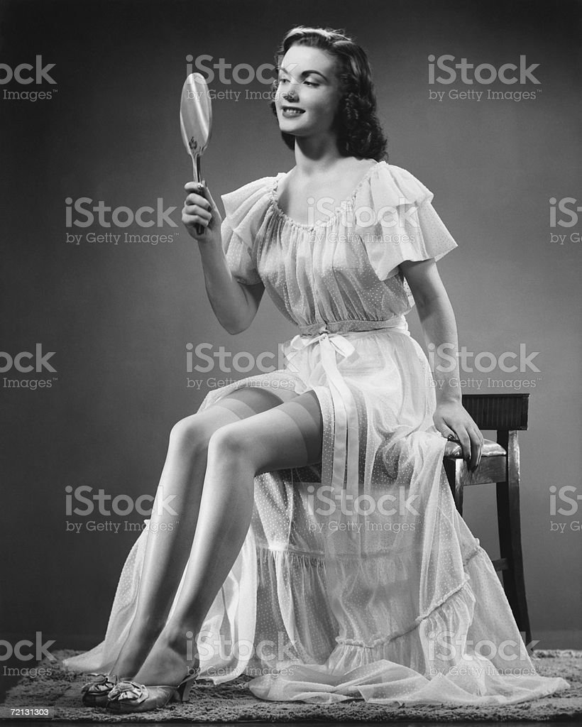 Woman looking at hand mirror (B&W) stock photo