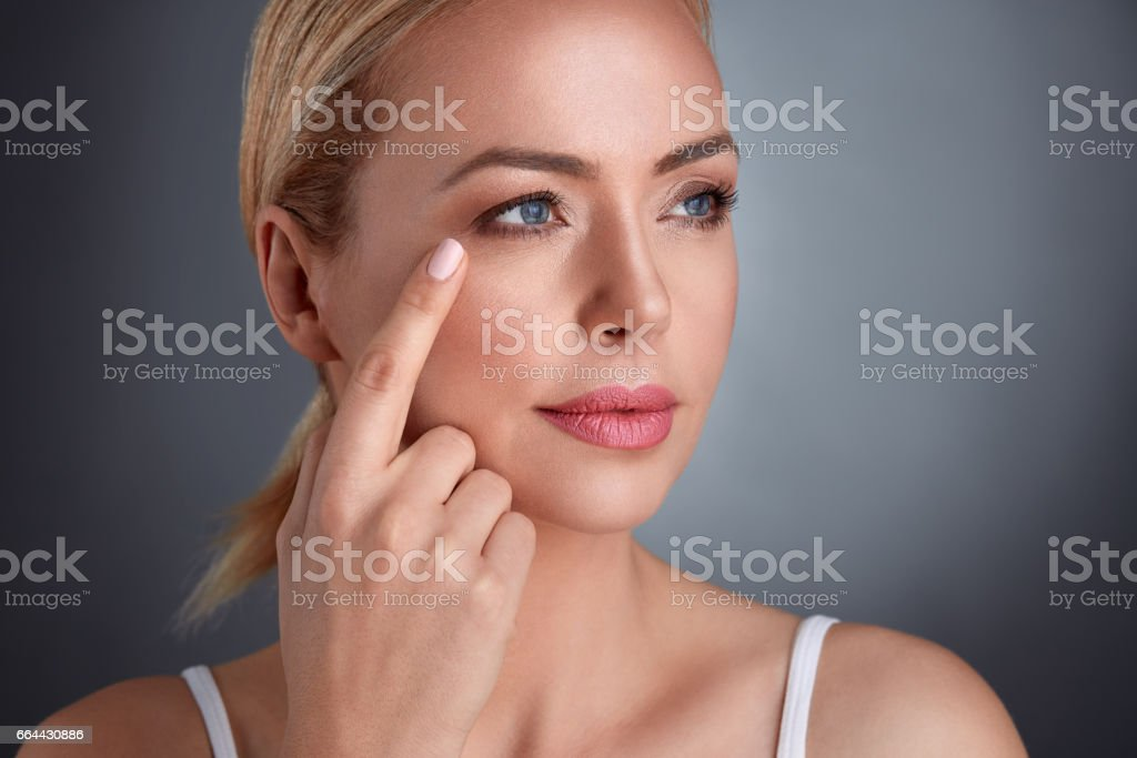 woman looking at her facial wrinkles stock photo