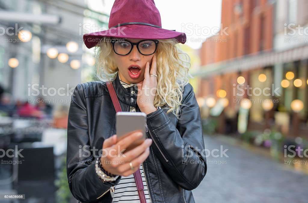 Woman looking at her phone in shock stock photo