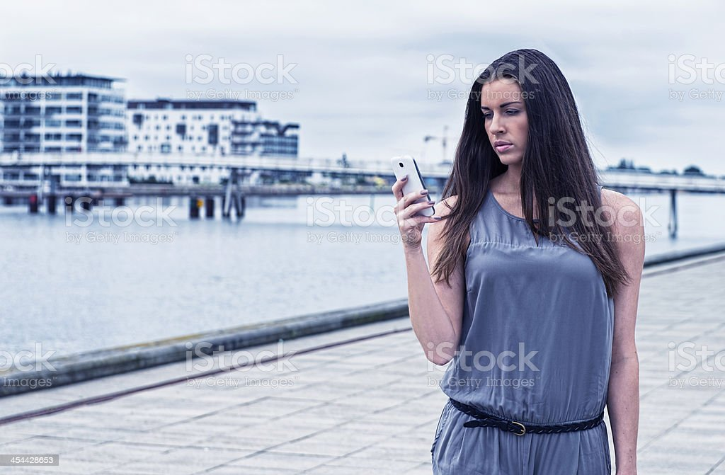 Woman looking at her phone while walking stock photo