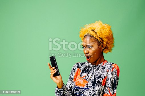 Woman looking at her phone with mouth wide open, isolated on green studio background