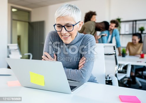 Woman looking at her work laptop while her colleagues discuss, joke and laugh.