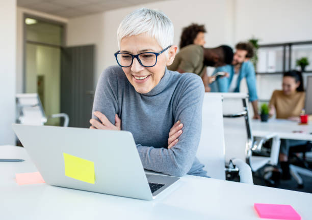 Woman looking at her work laptop while her colleagues discuss, joke and laugh. stock photo