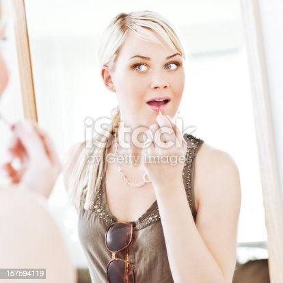 109721176istockphoto Woman looking at herself in a mirror applying lip gloss 157594119