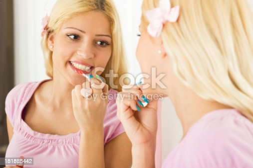109721176istockphoto Woman looking at herself in a mirror applying lip gloss. 181888442