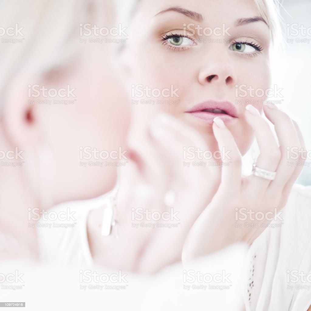 Woman looking at herself in a mirror royalty-free stock photo
