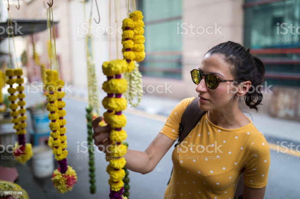 Young woman with sunglasses looking at Indian floral garland in Kuala...