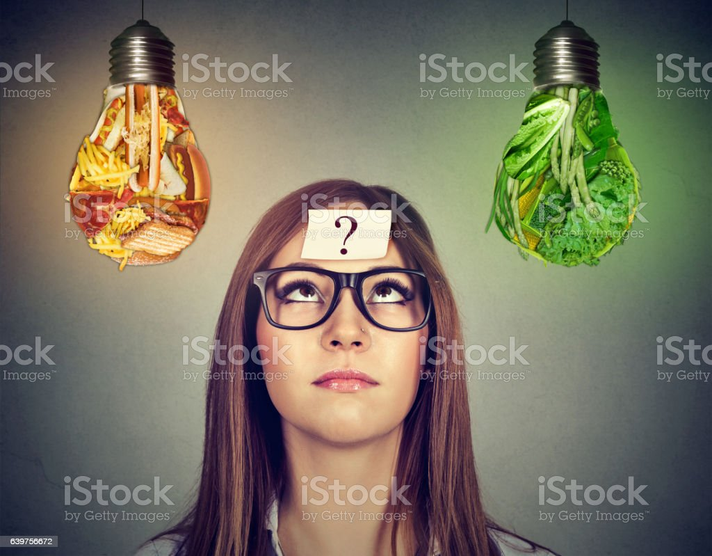 Woman looking at junk food and vegetables light bulb stock photo