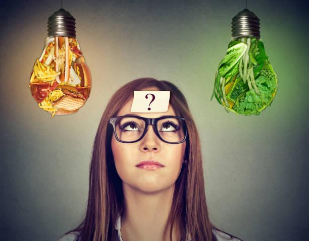woman looking at junk food and vegetables light bulb - gesundheitsfragen stock-fotos und bilder