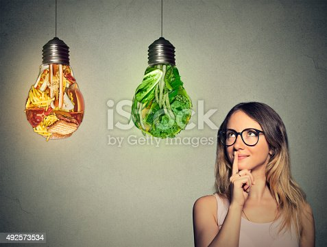 istock woman looking at junk food green vegetables shaped lightbulb 492573534