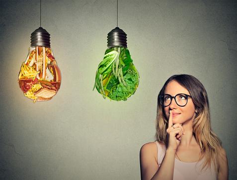 istock woman looking at junk food green vegetables shaped lightbulb 492573534