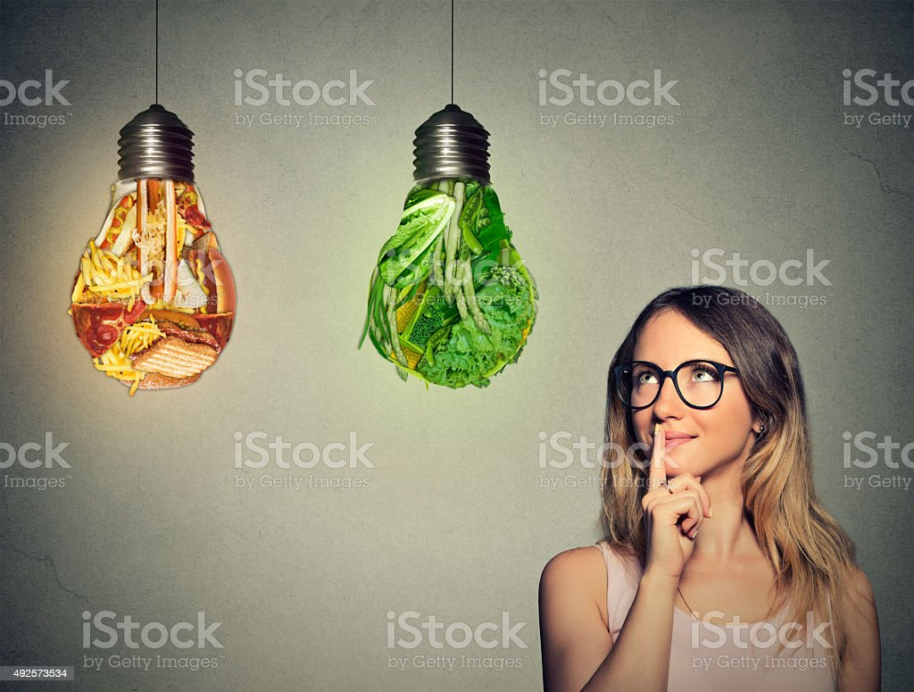 woman looking at junk food green vegetables shaped lightbulb stock photo